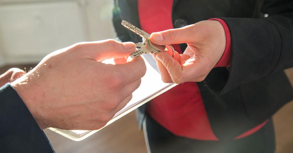 Eine Maklerin übergibt einem Mann die Wohnungschlüssel (gestellte Szene).