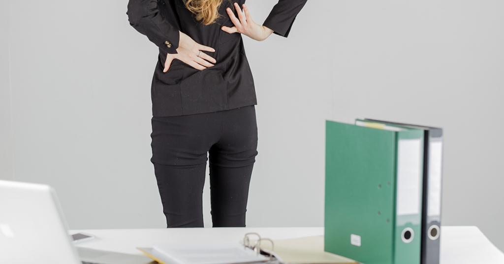 Eine Frau leidet bei der Arbeit an Rückenschmerzen.