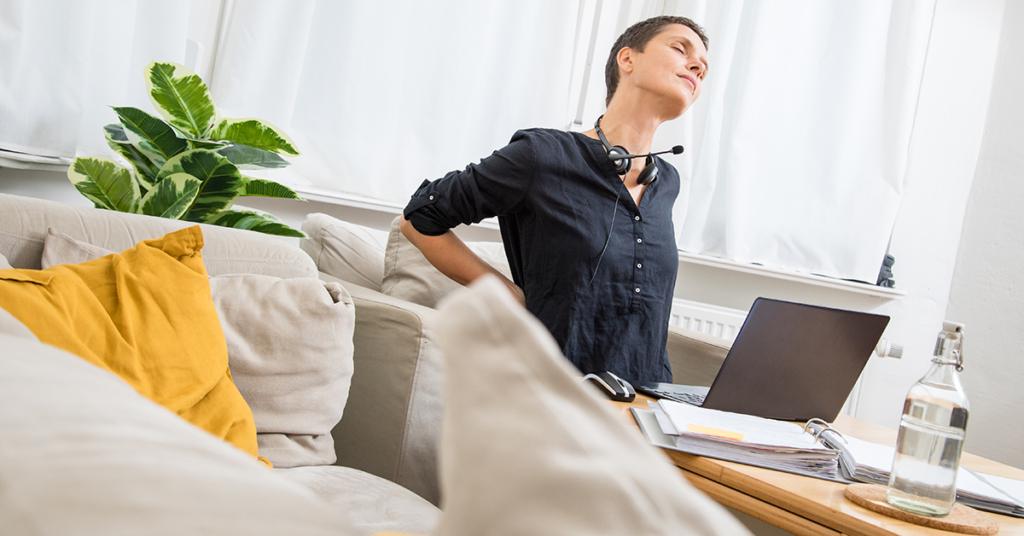 Eine Frau arbeitet auf einem Sofa im Home Office.