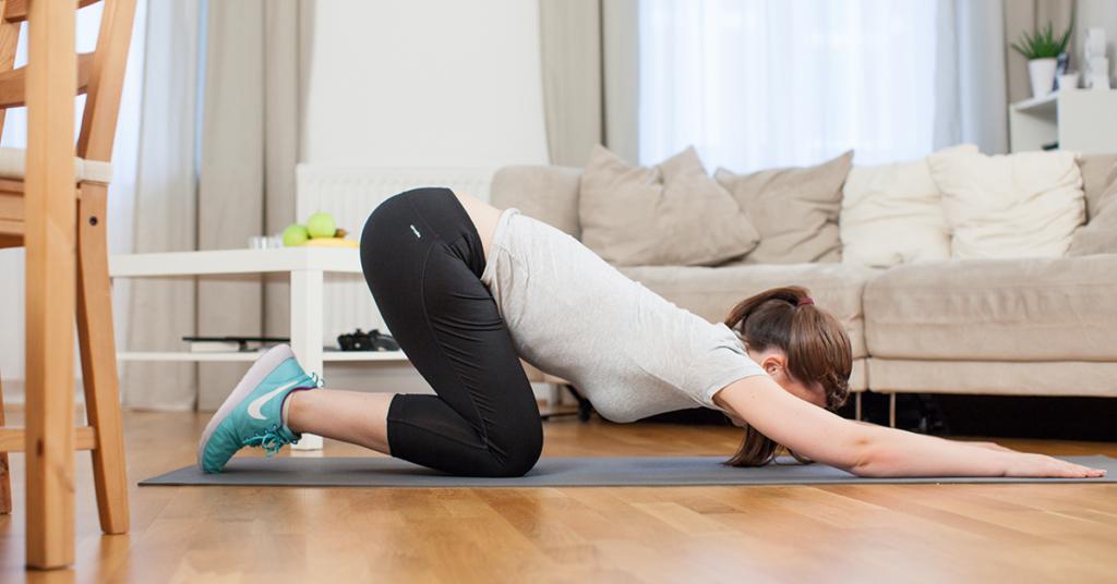 Eine junge Frau macht in einer Wohnung auf einer Fitnessmatte Rückenübungen