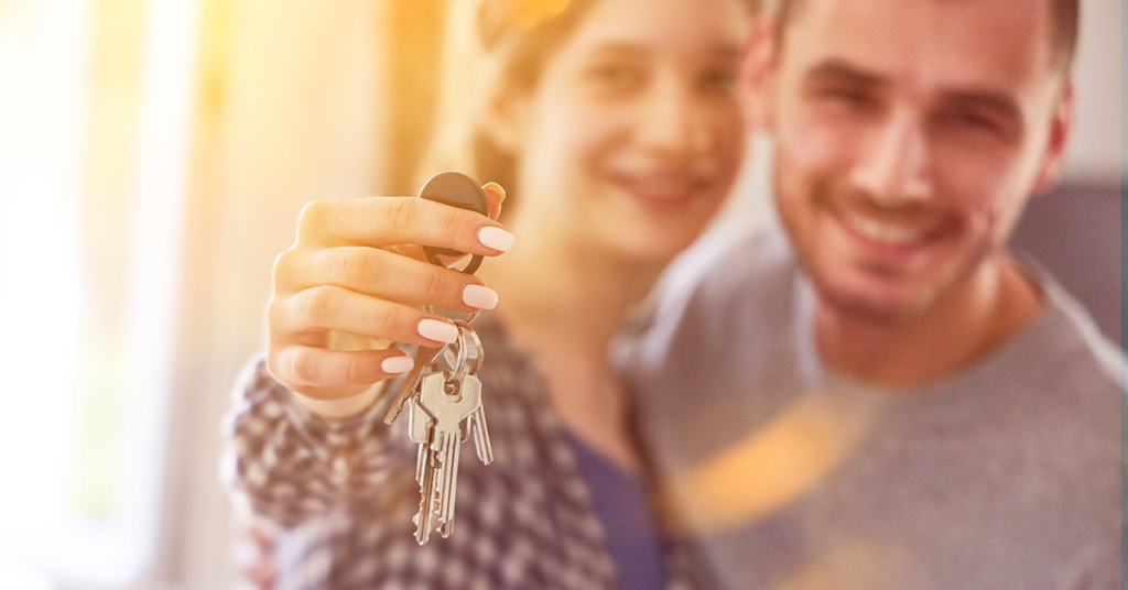 Glückliches Paar mit Schlüssel für Haus oder Wohnung nach dem Immobilienkauf